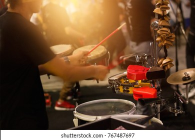 Man playing musical percussion instrument on street background, soft focus