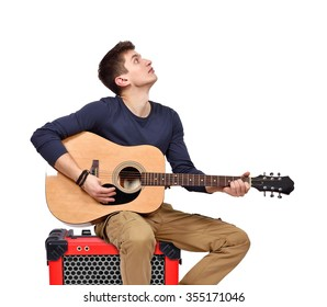 man playing on acoustic guitar sitting on red combo amp