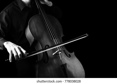 Man playing on cello on black background. String instruments
