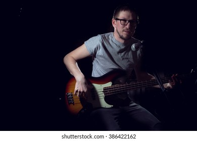 Man playing on electrical bass guitar on dark background
