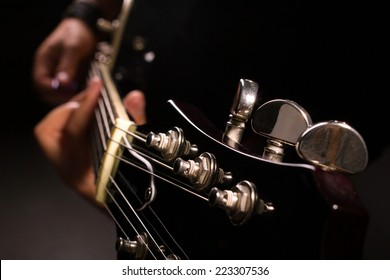 man playing on guitar on dark background, macro shot