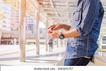man is playing on his mobile phone in the outdoor