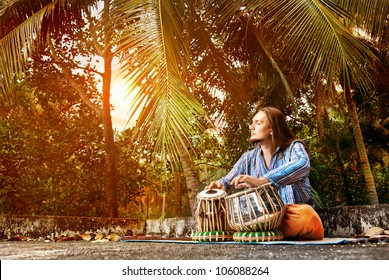 Man playing on traditional Indian tabla drums at sunset tropic background