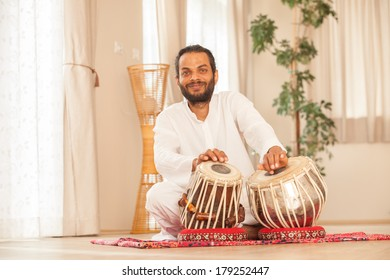 Man playing on traditional Indian tabla drums.