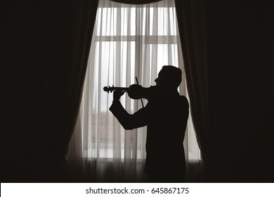 Man playing on violin near window. Silhouette.