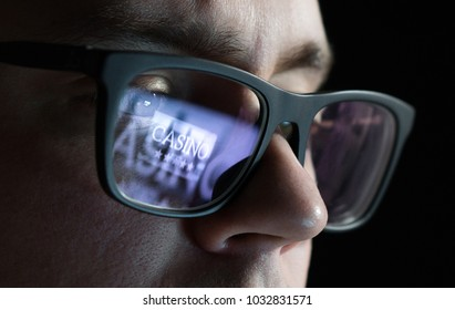 Man playing online casino games late at night. Gambling problem and addiction concept. Addict with reflection of laptop screen on glasses.