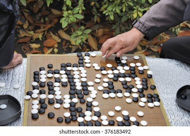Man playing in the outside Baduka that is the Korean name for Go