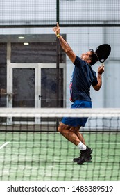 Man playing padel in a green grass padel court indoor behind the net
