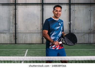 Man playing padel looking at camera while posing in a green grass padel court indoor behind the net