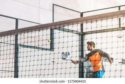 Man playing padel in a orange grass padel court outdoors behind the net