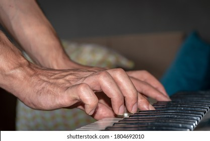 a man playing piano, hands only. extreme closeup.