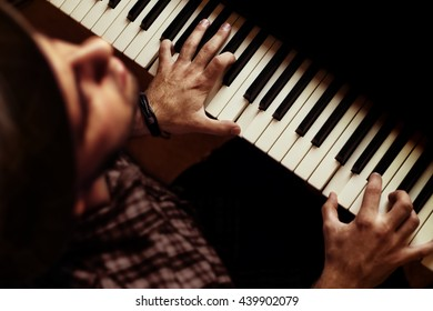 Man playing piano on dramatic dark stage