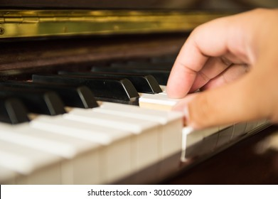 Man playing piano one hand, close up