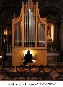 Man playing pipe organ in a church. Jeronimos monastery Lisbon, Portugal March 2019