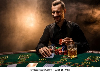 Man is playing poker with a cigar and a whiskey. A man winning all the chips on the table with thick cigarette smoke.
