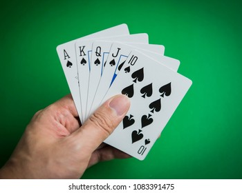 Man Playing Poker And Looking At Cards