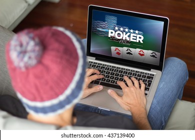 man playing poker online with laptop on the sofa. All screen graphics are made up.