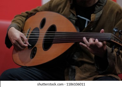 Man playing qanbus or gambus. Gambus is arabic music instrument shape like the guitar with rounded body.