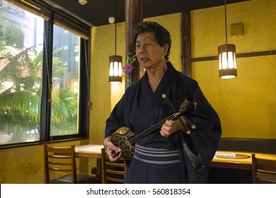 Man playing Sanshin in a restaurant at night, Okinawa, Japan - 04 Jan, 2017: Sanshin is an Okinawan musical instrument and precursor of the Japanese shamisen.