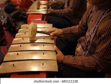 A man is playing saron, a Javanese gamelan musical instrument