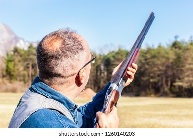 a man playing skeet or a hunter un the woods with a hunting rifle or shotgun on a sunny day