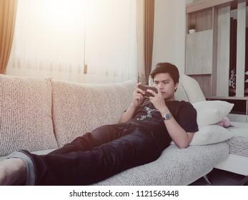 A man playing smartphone on sofa