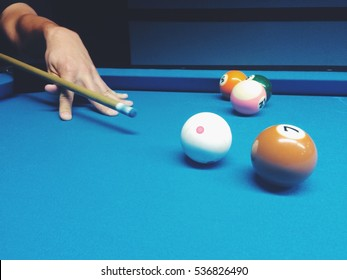 A man playing snooker at a blue table, aiming.