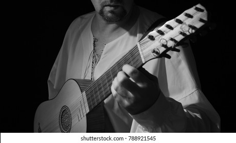 Man playing spanish renaissance instrument vihuela de mano over black