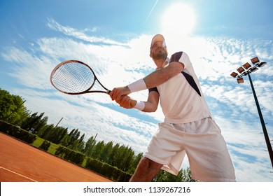 Man playing tennis in court in nature