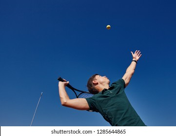 a Man playing tennis on the court on a beautiful sunny day