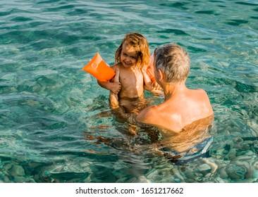 Man playing with toddler girl in sea - Cirali, Antalya Province, Turkey