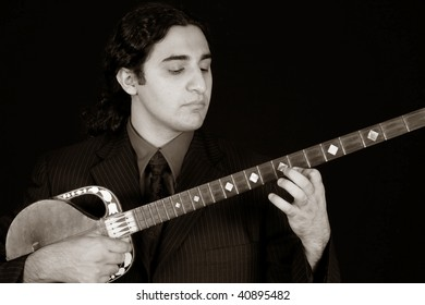man playing traditional eastern string instrument in sepia tone