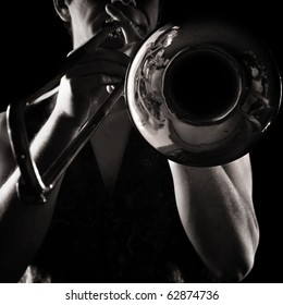 man playing a trombone; strong contrasting side-light; monochrome version;