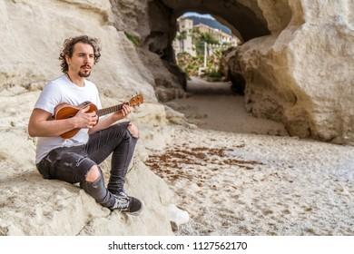 Man playing ukulele by the beach
