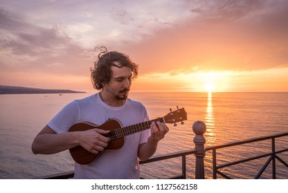 Man playing ukulele at sunset by the sea