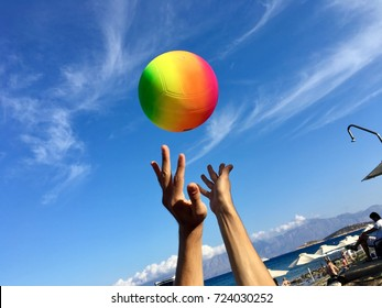 Man is playing valley with the colorful ball on the sky background