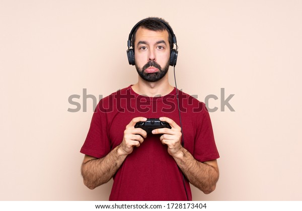Man playing with a video game controller over isolated wall with sad and depressed expression