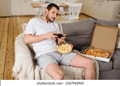 Man playing a video games at game console focused on the game and tense, eating popcorn and pizza. The concept of bachelor life man alone