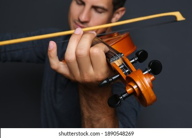 Man playing violin on black background, closeup
