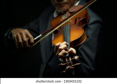 Man playing violin on dark tone