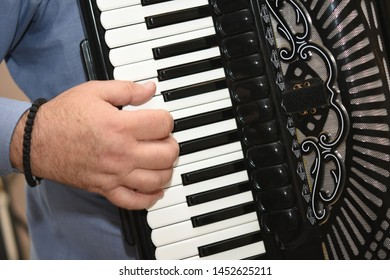 The man plays the accordion. fingers on the accordion