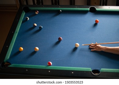 Man plays billiards on a blue table