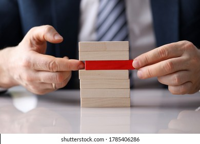 Man plays board game building from wooden blocks. Analysis situation and collection information. Competent management technology. Career breakthrough. Elimination symptoms and causes stress