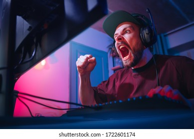 A man plays computer games at home. The guy is watching a video with headphones. The emotional player screams. Weekend at the screen. The irritated man lost.