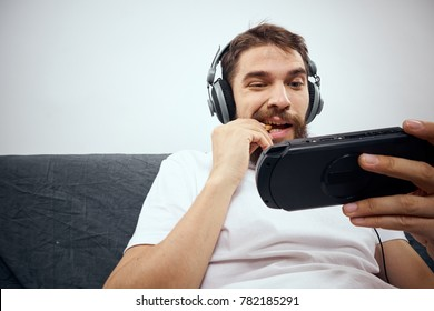 man plays the console, headphones