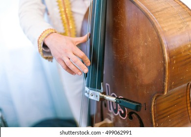 The man plays a contrabass. Acoustic double bass player