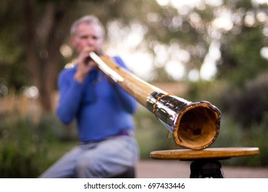 Man plays Didgeridoo in Garden