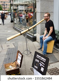 Man plays the didgeridoo, native to Australia on a pedestrian street in the tourist destination and famous historic town of Nuremburg, Germany.  August 2019.