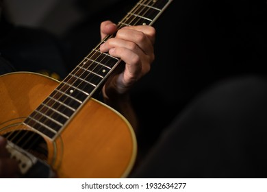 A man plays the guitar during a music session in a recording studio