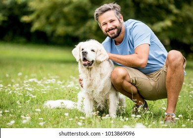 Man plays with his dog as friends together at garden in summer